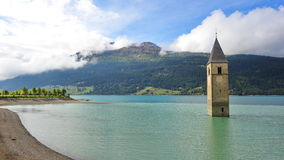 Ancient half-submerged bell tower in Graun im Vinschgau Stock Photos