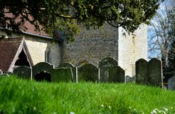 Ancient headstones in church cemetery. St James, Stedham, Sussex. Ancient grave headstones lined up in an orderly set of lines in the church grounds of St James royalty free stock photo