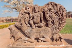 Ancient Hindu god sitting on myth lion creature, ruins of stone relief carvings from the 7th century temple, Karnataka. Stock Image