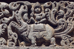 Ancient Hindu god sitting on myth lion creature, sculpured stone relief carvings from temple`s wall, India Stock Photo
