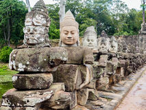 Ancient Hindu statutes in Cambodia. Statutes of stone diva or gods with original and newly moulded heads at Angkor Thom, ancient capital of Khmer empire Stock Photos