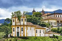 Ancient historical churches among the houses and streets of Ouro Preto city in Minas Gerais. With hills and clouds in the background stock photo