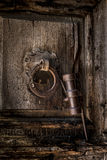 Ancient Holy Door. A door knocker, etched in Arabic, with Roman letters carbed below in the wood.  The 'key holder' is attached to the door knocker, on the door Stock Photography