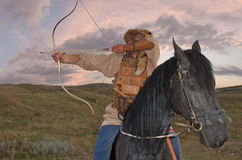 Ancient horseman weaponed with arc. Sunset clouds Stock Photography