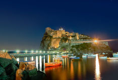 Ancient hotel and castle in Ischia island, Italy, at night. There are a lot of boats in the sea royalty free stock images