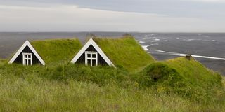 Ancient houses with Grass roof in iceland, overlooking a black s royalty free stock photos