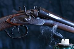Old Hunting Shotgun. Ancient hunting shotgun closeup near extinguished candle on dark background Stock Photos