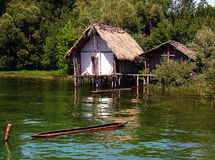 Ancient hut on piles at a green lake. White house on piles at a green lake with a canoe Stock Images