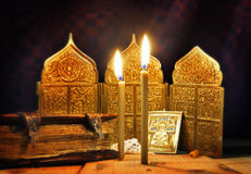 Ancient icons and burning candles. Focus on candles Royalty Free Stock Photography