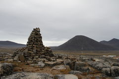 An ancient Inuit inukshuk inuksuk that serves as a landmark for travellers, located near Qikiqtarjuaq, Baffin Island. Nunavut, Canada Stock Photography
