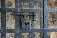 Ancient iron lock with latch on aged boarded door. Royalty Free Stock Images