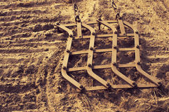 Ancient iron plow on the earth in the spring. Harrow. Royalty Free Stock Photo