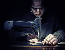 Ancient job. Detail on man sew with old machine stock image