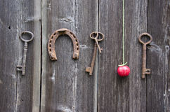 Ancient key, horseshoe and red apple on old wooden wall Stock Photos