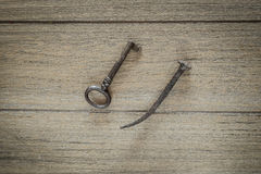 Ancient key and old bent nail on wooden background Royalty Free Stock Images