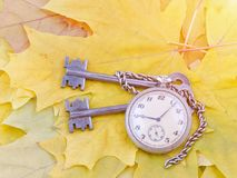 Ancient keys and a pocket watch lie on yellow maple autumn leaves.  Stock Photography