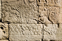 Ancient Khmer carving Deer Hunter. Ancient Khmer carving of a man hunting a deer in the woods with a rabbit nibbling the grass.  Wall of Bayon Temple, Angkor Royalty Free Stock Image