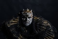 Ancient king of fairy tale world sitting on throne, fantasy concept. Old bearded blind man thorns on his head isolated. On black background. Creepy magician in stock image