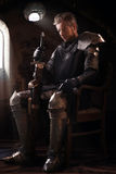 Ancient knight in metal armor. Sitting on a wooden chair in a palace Stock Photos
