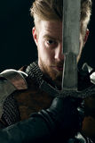 Ancient knight in metal armor. With sword on gray background Stock Photos