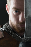 Ancient knight in metal armor. With sword on gray background Stock Photo