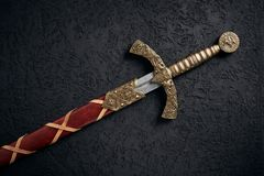 Ancient knightly sword of the era of the Crusades in the Middle Ages. The Knights Templar against a dark background royalty free stock photography
