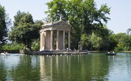 Ancient lake. Park Villa Borghese, Rome, Italy. A little pond with boats in which lovers can cross the water to reach the island with ancient temple Royalty Free Stock Image
