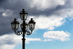 Ancient lamppost against a cloudy sky Royalty Free Stock Images