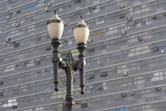 Ancient lamppost  in contrast to facade of building. Ancient lamppost, typical of the city of Sao Paulo, in contrast to facade of building royalty free stock photo