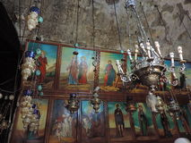 Ancient lamps and paintings in the Church of the Sepulchre of Saint Mary. Ancient lamps and various paintings hanging on the wall of the Church of the Sepulchre Royalty Free Stock Image