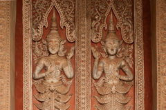 Ancient Laos art wood carving on church in Hor Phakaeo temple. Royalty Free Stock Photo