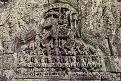 An ancient lintel partly covered with green lichen in Angkor Wat stock photography