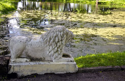 Ancient lion sculpture near old pond in park Royalty Free Stock Photo