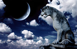 Ancient lion statue and bright moon in the night sky Stock Photos