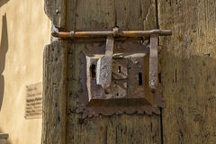 Ancient lock with latch on aged boarded door. Royalty Free Stock Photography
