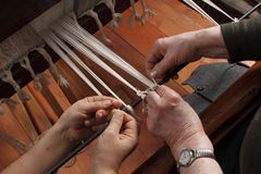Ancient loom. Two persons work on ancient loom stock photography