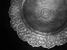 Ancient Malay silver plate. An image of an antique silver plate of the Malay ethnic people. Taken on black velvet. Plate is heavy silver, with patterns of royalty free stock image