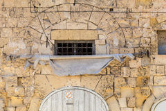 Ancient Maltese limestone house frontage with arch and frayed aw. Yellow weathered limestone building, with frayed white sun-shade and arches, shot straight-on Royalty Free Stock Photography