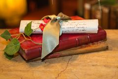 Ancient Manuscript Parchment Scroll, Rolled Up with Golden Ribbo. N and Red Book and Green Leaves Royalty Free Stock Images
