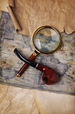 Ancient map, magnifying glass and smoking pipe Royalty Free Stock Image