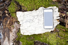 Ancient map and smartphone in autumn forest. royalty free stock photography