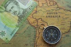Ancient map of South America with Chilean money and a compass, close-up stock photos