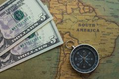 Ancient map of South America with usa money and a compass, close-up stock image