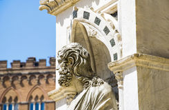 The ancient marble portrait of man with palace on background in Siena, Italy stock photo