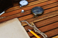 Ancient mariner's compass and watch. Ancient mariner's compass, watch and old paper on wooden background Stock Image