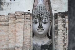 Ancient marvellous stone buddha head statue surrounding by triangle great stone wall at Wat Sri Chum, Sukhothai, Thailand Stock Images