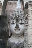 Ancient marvellous stone buddha head statue surrounding by triangle great stone wall at Wat Sri Chum, Sukhothai, Thailand Stock Image