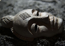 Ancient Mask. This is a replica mask decoration lying in volcanic sands Royalty Free Stock Image