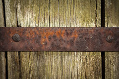 Ancient medieval background. Old rusty metal plate with copy space on weathered wooden surface Royalty Free Stock Images