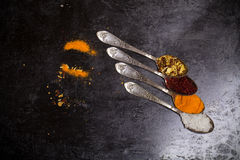 Ancient melchior spoons with spices on metal surface for backgro. Und. Toned Royalty Free Stock Photo